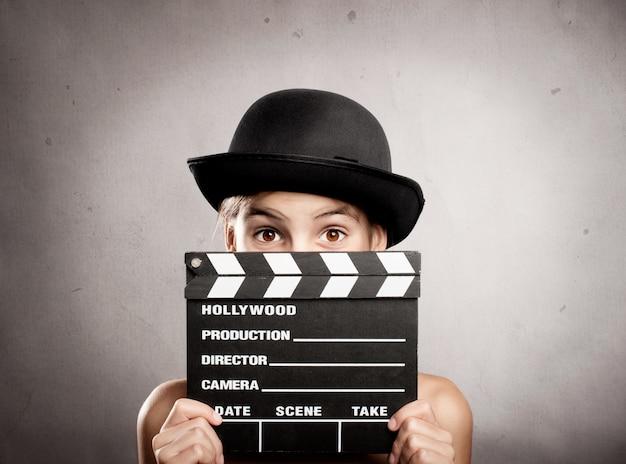 Klein meisje met een film klepel bord op een grijze achtergrond