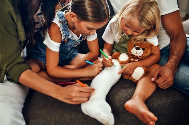 Klein meisje met een gebroken been op de bank. moeder, vader en twee dochters tekenen op gips met viltstiften. het hele gezin vermaakt zich thuis.