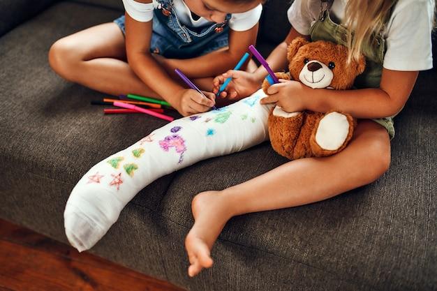 Klein meisje met een gebroken been op de bank. twee zussen tekenen met viltstiften op een gipsverband. kinderen hebben plezier en spelen op de bank in de woonkamer.