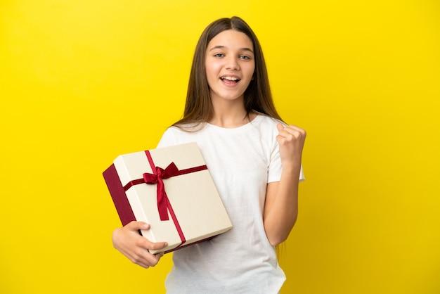 Klein meisje met een geschenk over een geïsoleerde gele achtergrond die een overwinning viert in winnaarspositie