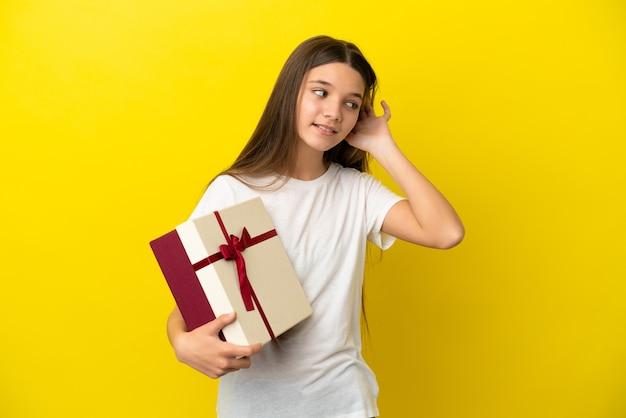 Klein meisje met een geschenk over een geïsoleerde gele achtergrond die naar iets luistert door de hand op het oor te leggen