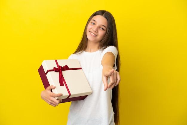 Klein meisje met een geschenk over een geïsoleerde gele achtergrond die naar voren wijst met een gelukkige uitdrukking