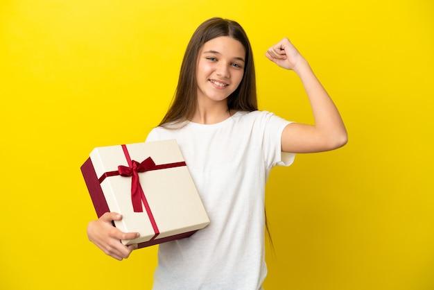 Klein meisje met een geschenk over geïsoleerde gele achtergrond die een overwinning viert