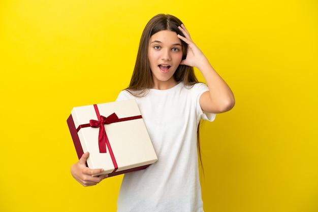 Klein meisje met een geschenk over geïsoleerde gele achtergrond met verrassingsuitdrukking