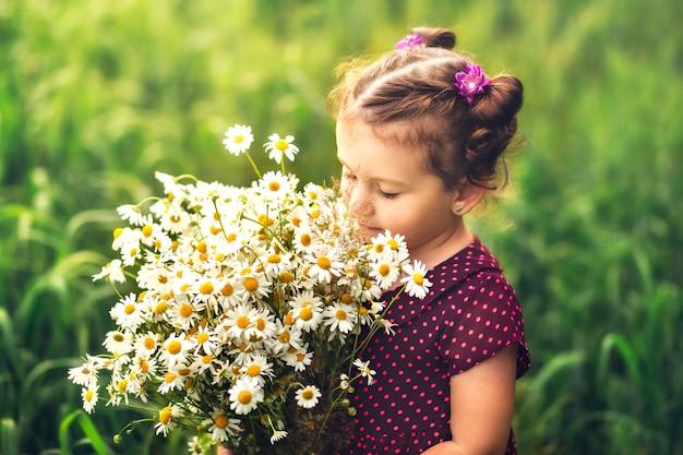 Klein meisje met een groot boeket van madeliefjes bloemen