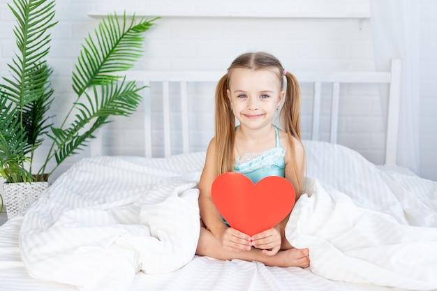 Klein meisje met een groot rood hart in haar handen om thuis op het bed op een wit katoenen bed te zitten en lief te glimlachen, valentijnsdagconcept