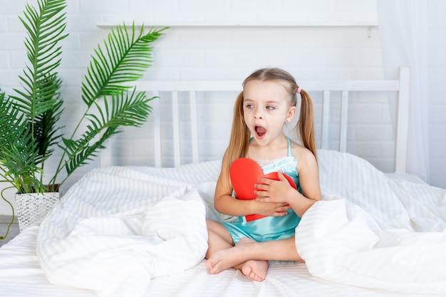 Klein meisje met een groot rood hart in haar handen om thuis op het bed op een wit katoenen bed te zitten en schattig, valentijnsdagconcept te gapen