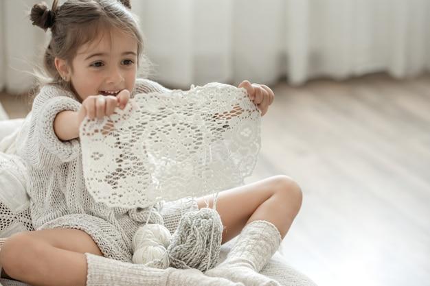 Klein meisje met een kanten servet van natuurlijk katoengaren, met de hand gehaakt. haken als hobby.