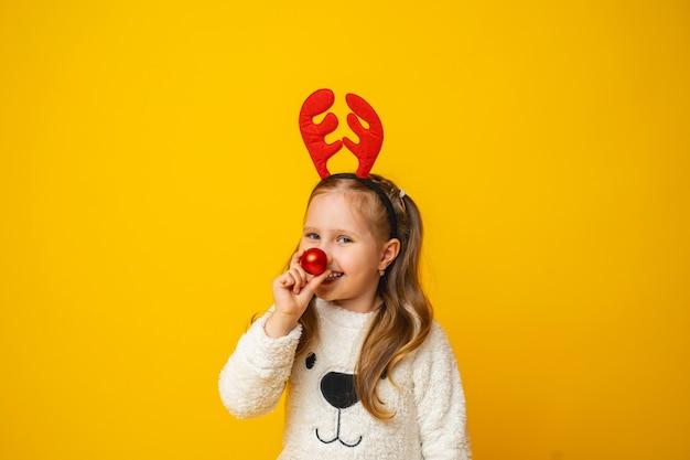 Klein meisje met een kerstbal op haar neus