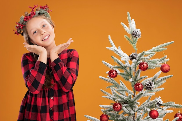 Klein meisje met een kerstkrans in een geruit hemd, blij en positief glimlachend naast een kerstboom over een oranje muur