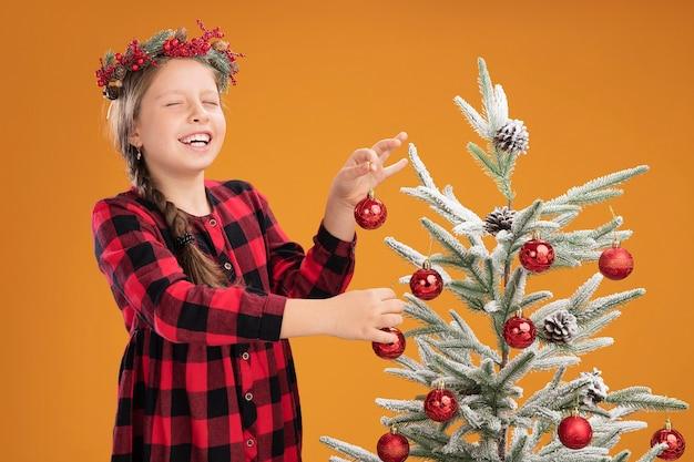 Klein meisje met een kerstkrans in een geruite jurk die de kerstboom verfraait, blij en vrolijk boven de oranje muur staat
