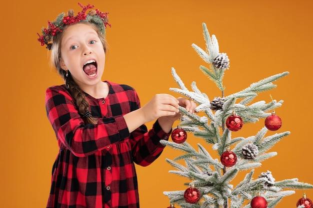 Klein meisje met een kerstkrans in een geruite jurk die de kerstboom versiert, blij en vrolijk die tong uitsteekt over de oranje muur