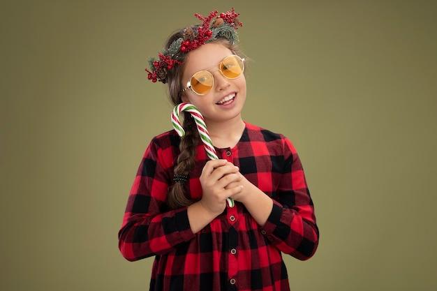 Klein meisje met een kerstkrans in een geruite jurk met snoepgoed, blij en positief glimlachend, vrolijk over de groene muur