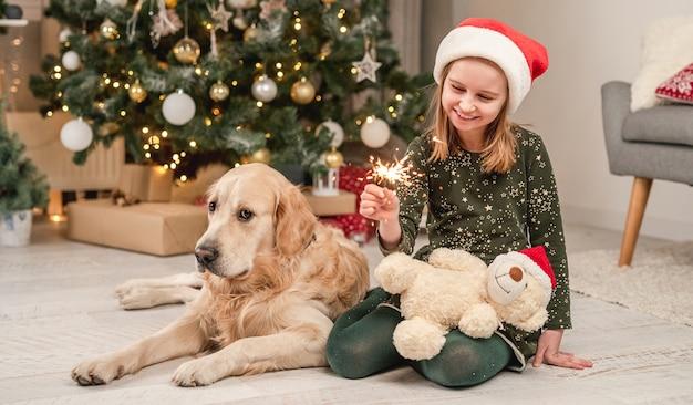 Klein meisje met een kerstmuts met een sterretje dat thuis naast een golden retrieverhond onder de kerstboom zit