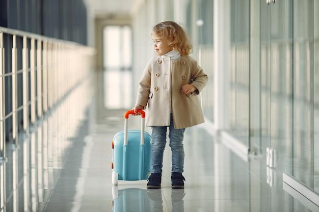 Klein meisje met een koffer op de luchthaven