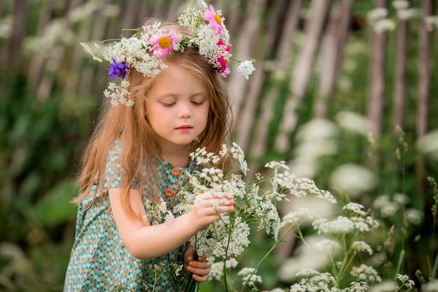 Klein meisje met een krans van bloemen op haar hoofd voor een wandeling