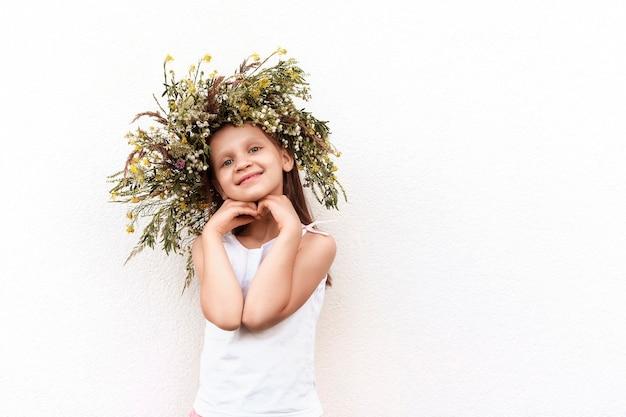 Klein meisje met een krans van wilde bloemen op een witte achtergrond