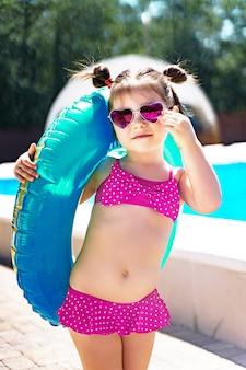 Klein meisje met een opblaasbare ring in een zwembroek staat bij het zwembad