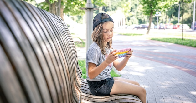 Klein meisje met een pet gebruikt een smartphone die op een zomerdag op een bankje in het park zit.