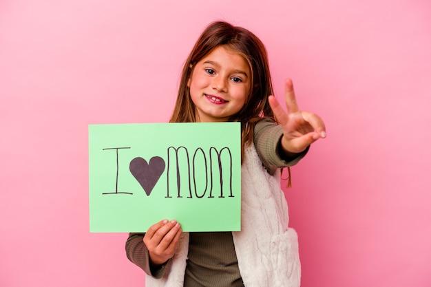 Klein meisje met een plakkaat ik hou van mama geïsoleerd op roze achtergrond
