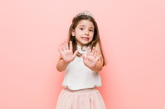Klein meisje met een prinses-look die iemand afwijst die een gebaar van walging toont. Premium Foto
