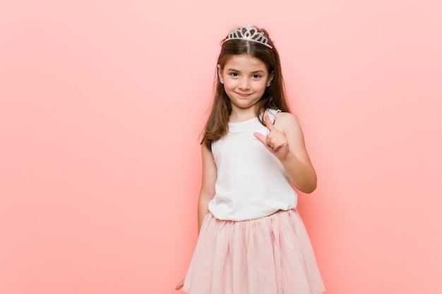 Klein meisje met een prinses-look die met de vinger naar je wijst alsof het uitnodigt dichterbij te komen. Premium Foto