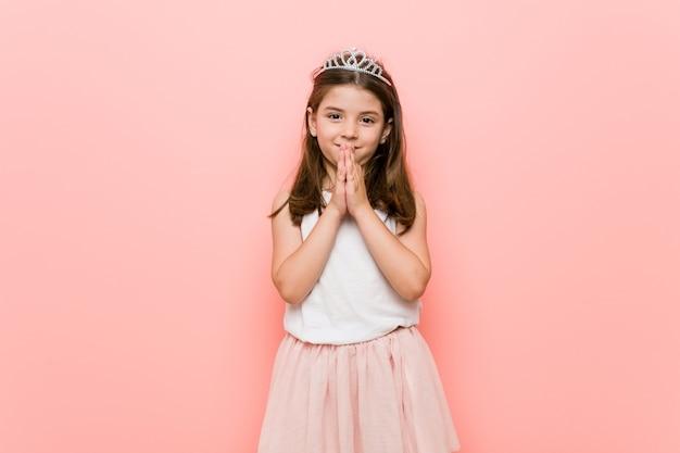 Klein meisje met een prinses-look hand in hand bidden in de buurt van de mond, voelt zich zelfverzekerd.