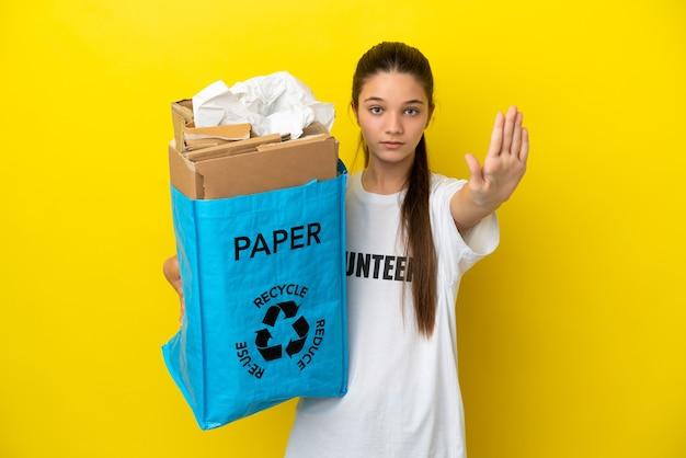 Klein meisje met een recyclingzak vol papier om over een geïsoleerde gele achtergrond te recyclen en een stopgebaar te maken