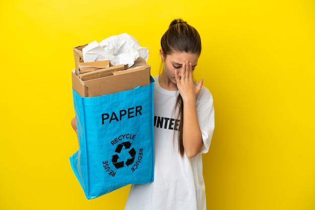 Klein meisje met een recyclingzak vol papier om te recyclen over geïsoleerde gele achtergrond met vermoeide en zieke uitdrukking