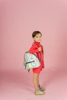 Klein meisje met een rugzak op een pastel roze achtergrond