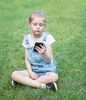 Klein meisje met een smartphone in het park the