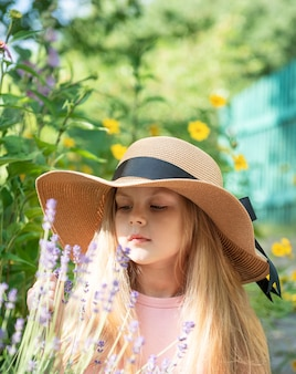 Klein meisje met een strohoed omringd door lavendelbloemen