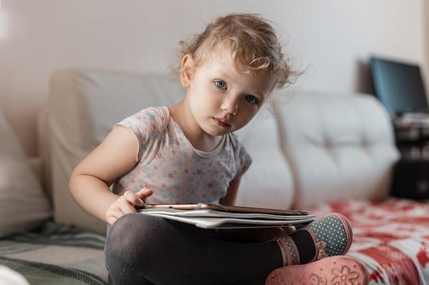 Klein meisje met een tablet zit op de bank, studeert thuis