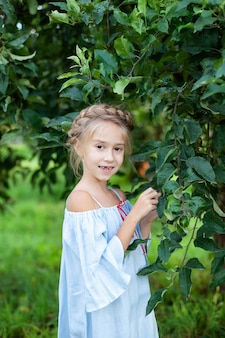 Klein meisje met een varkensstaart op haar hoofd is waard in appelboomgaard. kind wandelingen in het bos in de lente. zomervakantie.