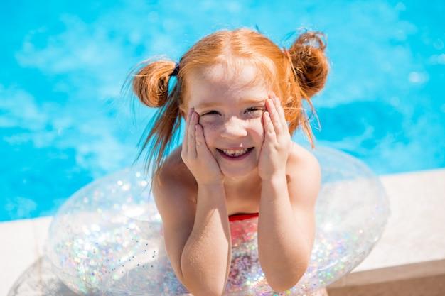 Klein meisje met een zwemmende cirkel in het zwembad
