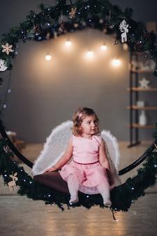 Klein meisje met engelenvleugels zittend op spar krans.