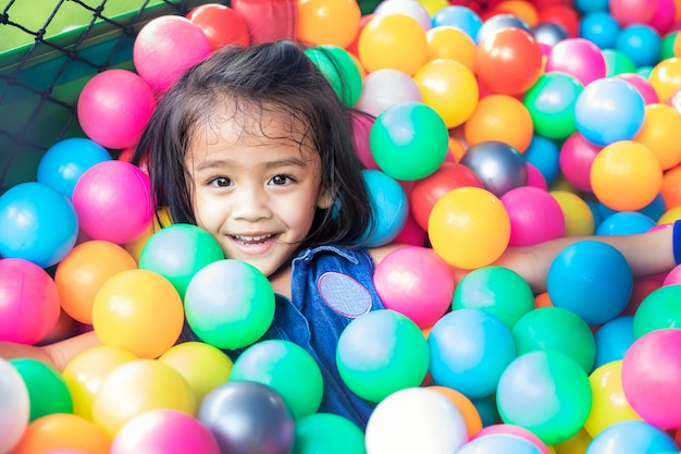 Klein meisje met gekleurde plastic ballen. grappig kind plezier binnenshuis.