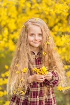 Klein meisje met gele bloemen in haar handen. een kind op een achtergrond van gele bloemen. lente portret van een kind