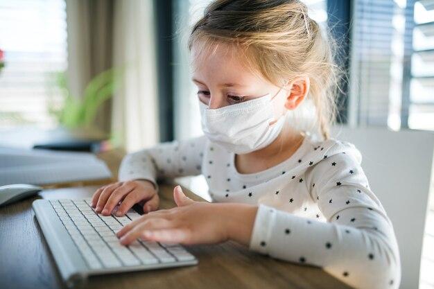 Klein meisje met gezichtsmasker met behulp van computer binnenshuis op kantoor aan huis, corona virus en quarantaine concept.