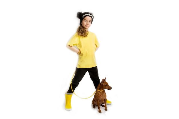 Klein meisje met haar hond, zwarte en gele kleren. witte achtergrond. studio-opnamen. baby huisdieren concept. hoge kwaliteit foto
