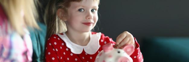 Klein meisje met haar moeder gooit munt in roze spaarvarken