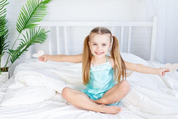 Klein meisje met harten in haar handen om thuis op het bed op een wit katoenen bed te zitten en zoet te glimlachen, valentijnsdagconcept
