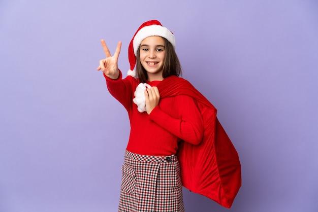 Klein meisje met hoed en kerstzak geïsoleerd op paarse achtergrond glimlachend en overwinningsteken tonen