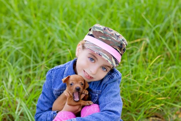 Klein meisje met huisdier puppy mascotte mini pinscher