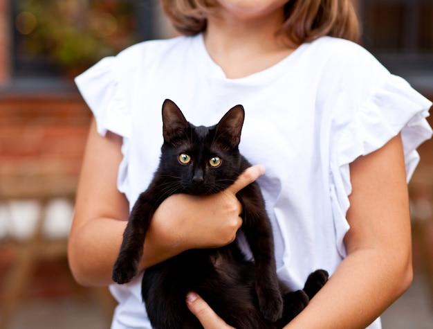Klein meisje met huisdierenvriend zwarte kat