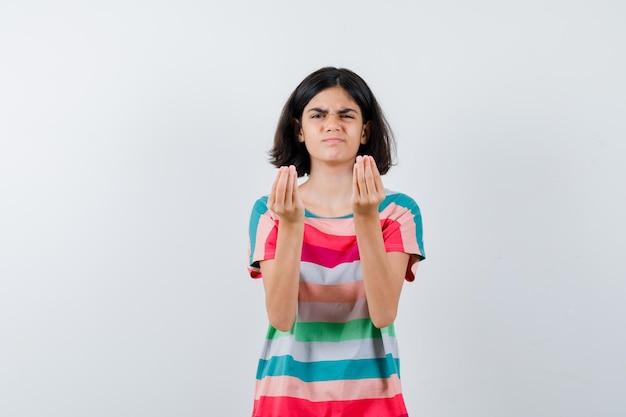 Klein meisje met italiaans gebaar, grimassen in t-shirt, spijkerbroek en ontevreden kijken. vooraanzicht.