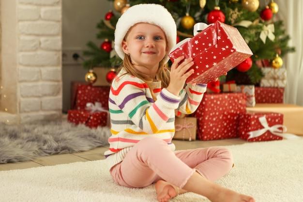 Klein meisje met kerstcadeaus in kerstinterieur