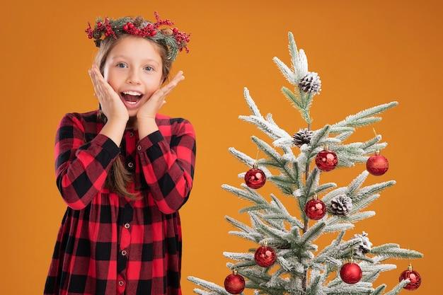 Klein meisje met kerstkrans in geruit overhemd, blij en opgewonden naast een kerstboom over oranje muur