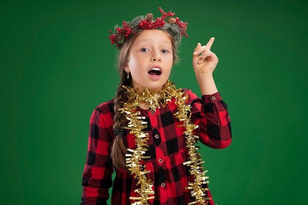 Klein meisje met kerstkrans in geruite jurk met klatergoud om nek met glimlach op verrast gezicht met wijsvinger met geweldig idee over groene muur