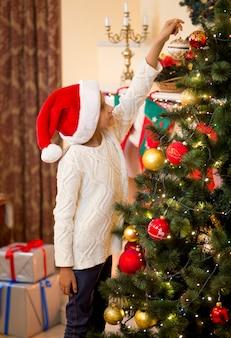 Klein meisje met kerstmuts die gouden bal bovenop de kerstboom zet